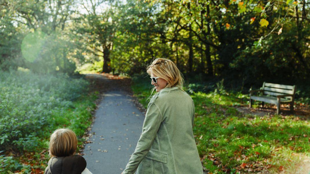 mama cu copil se plimba in parc