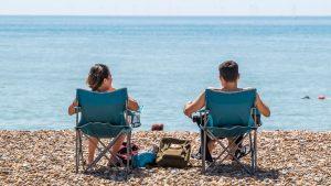 doi tineri stau pe sezlong la plaja
