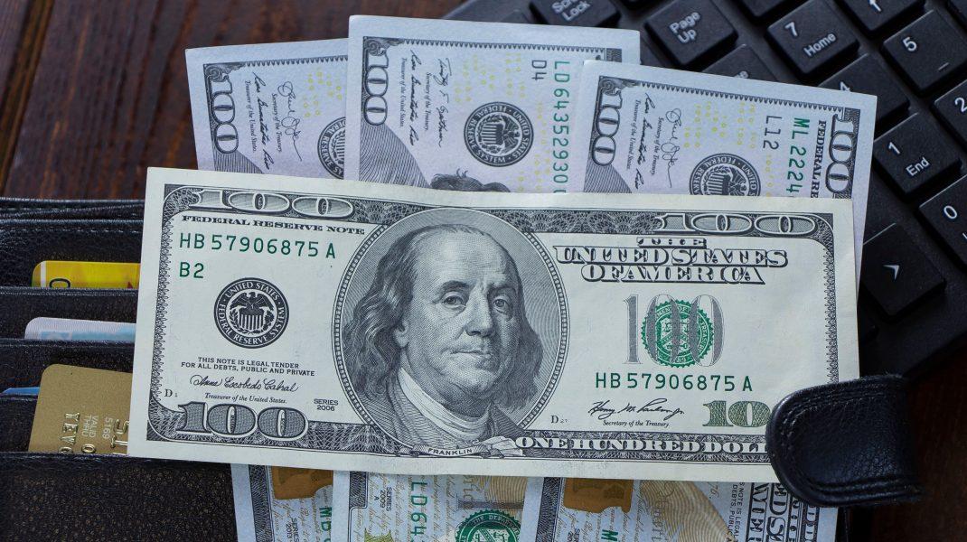 bancnote de dolari peste un laptop.