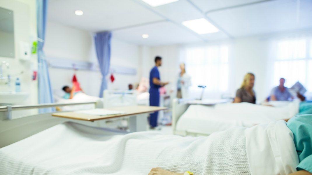 Bărbat întins pe patul de spital așteptând transplant