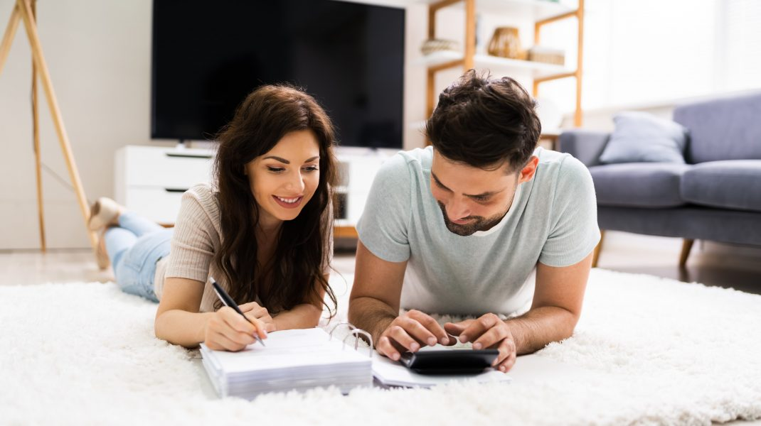 doi tineri care calculeaza un buget intr-o casa noua.