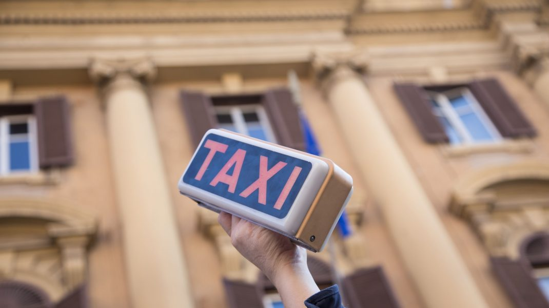 semn de taxi tinut in mana la un protest