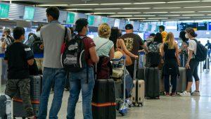 Oameni care stau la coadă în aeroport.