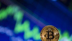 moneda bitcoin cu un grafic in fundal.