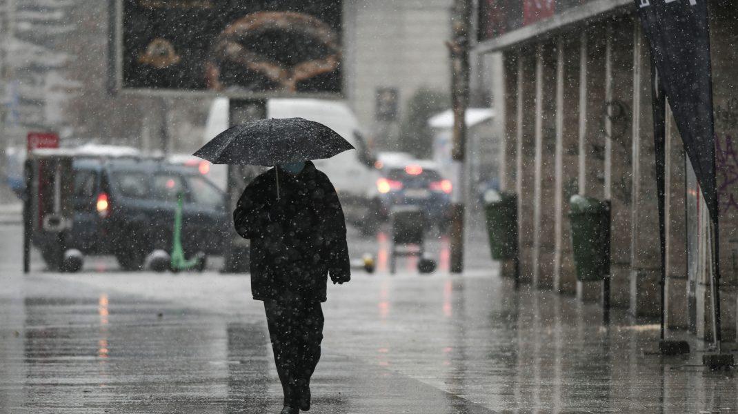 Bărbat care merge pe stradă și ține o umbrelă în mână.