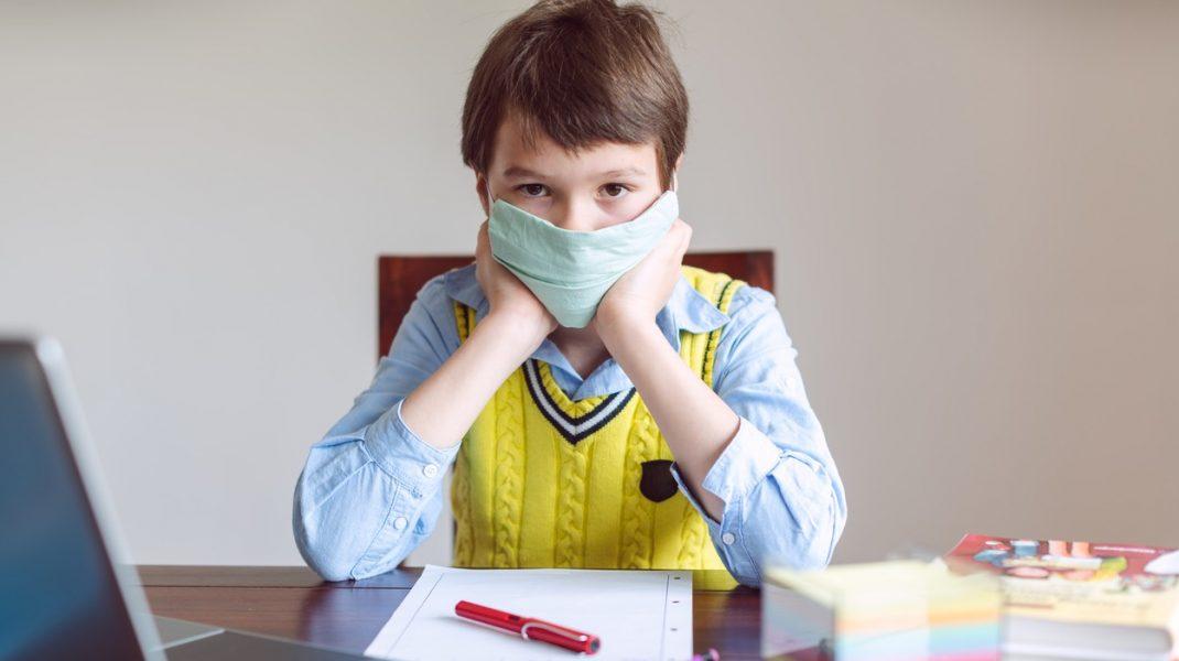 Copil care stă la birou, pregătit pentru școala online, cu mască de protecție.