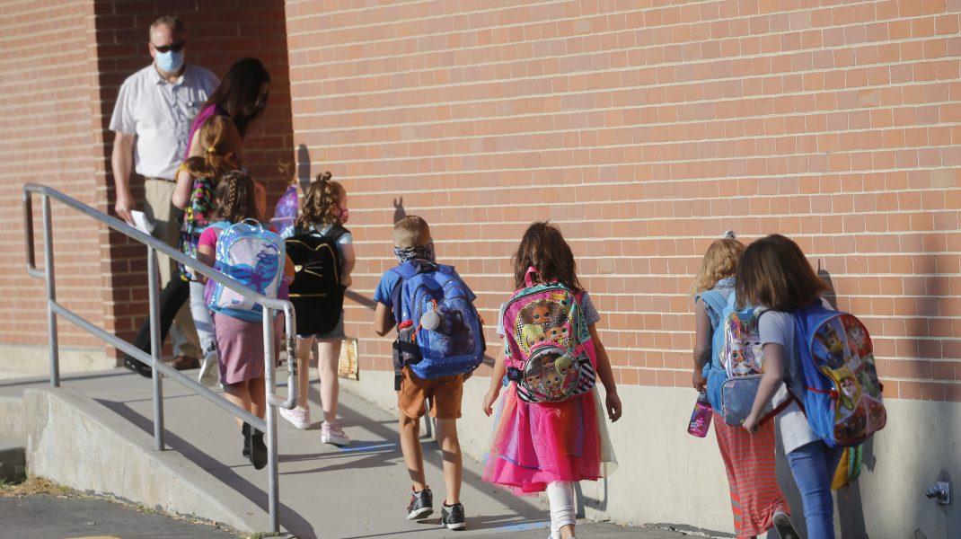 școlari mergând pe trotuar