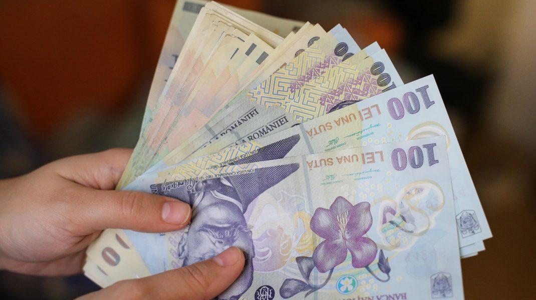 Bani în mâna unei persoane.