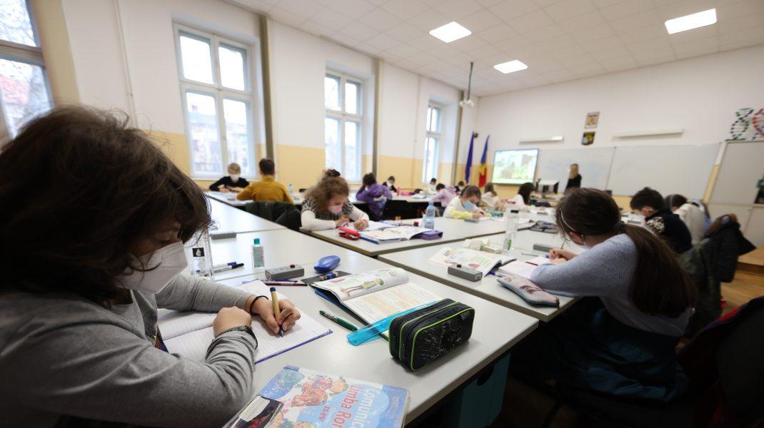 Elevi cu mască în sala de clasă.