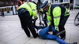 Imaginile care au stârnit indignare. O femeie a fost dezbrăcată și târâtă de poliție, în timpul unui protest din Manchester