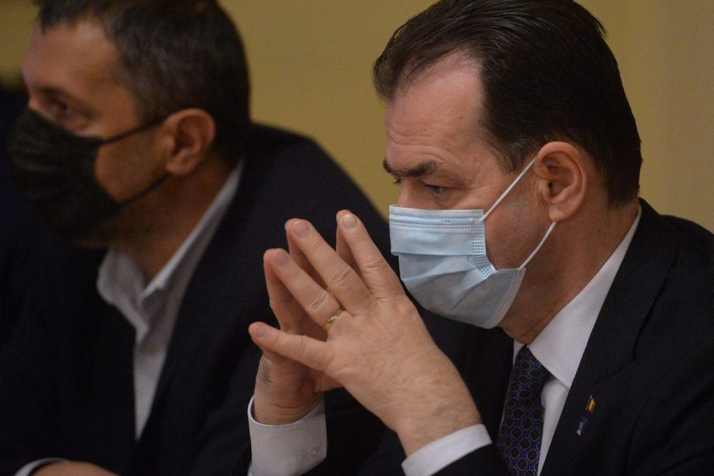 Ludovic Orban poartă mască și ține palmele împreunate în timp ce se uită într-un punct fix.