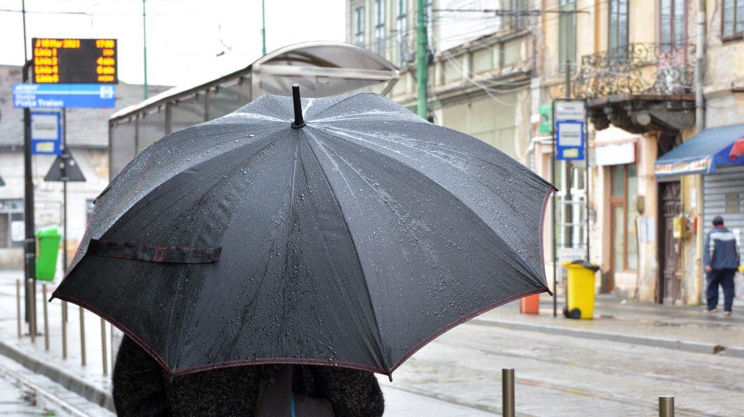 o femeie tine o umbrela in ploaie.