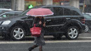 O femeie merge prin ploaie sub umbrelă.