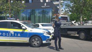 politista sexy in fata masinii de politie.
