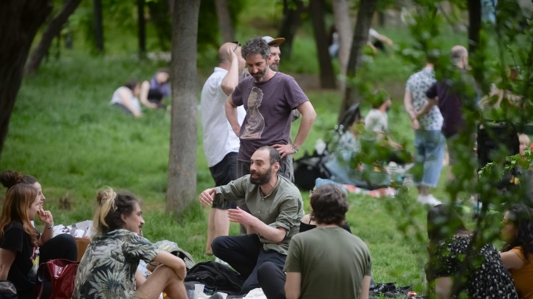 Un grup de tineri se află la picnic în Parcul Cișmigiu din București