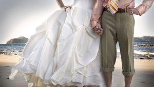 Bărbat și femeie ținându-se de mână. Femeia este îmbrăcată în rochie de mireasă.