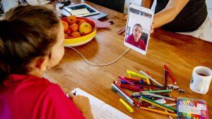 Copil care participă la școala online și are pe masă creioane și caiete.