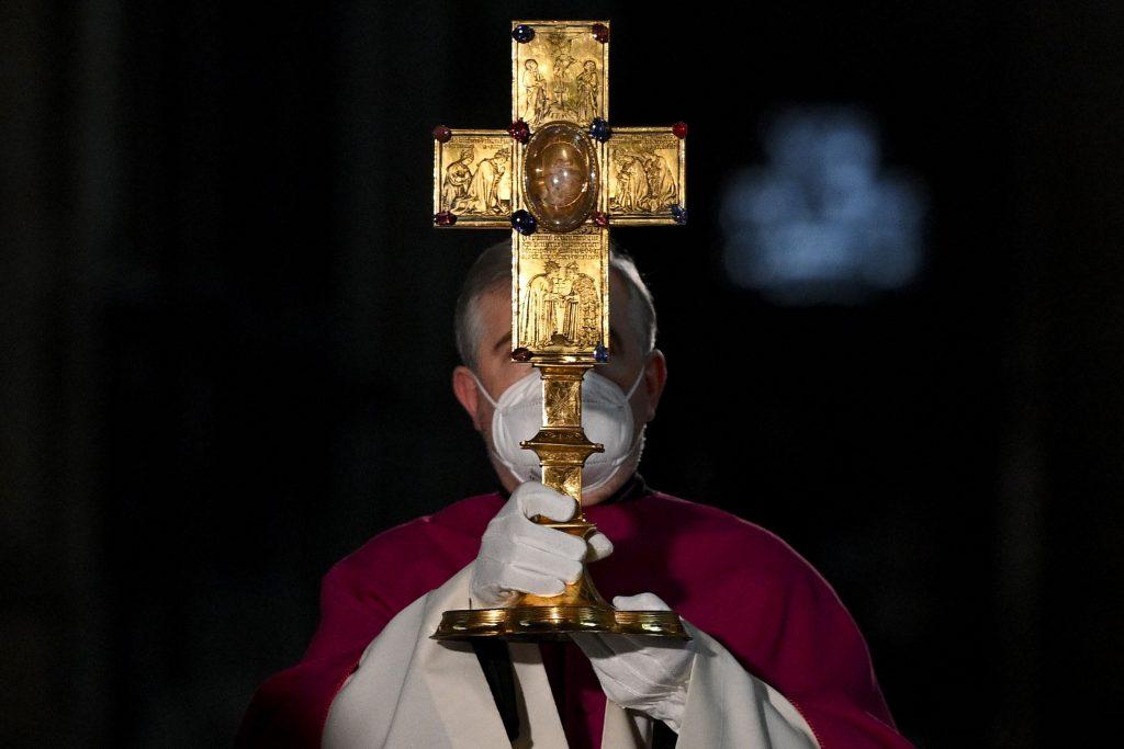 Preot care are în mână o cruce mare de aur.