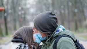 Cuplu care se sărută purtând măști de protecție.