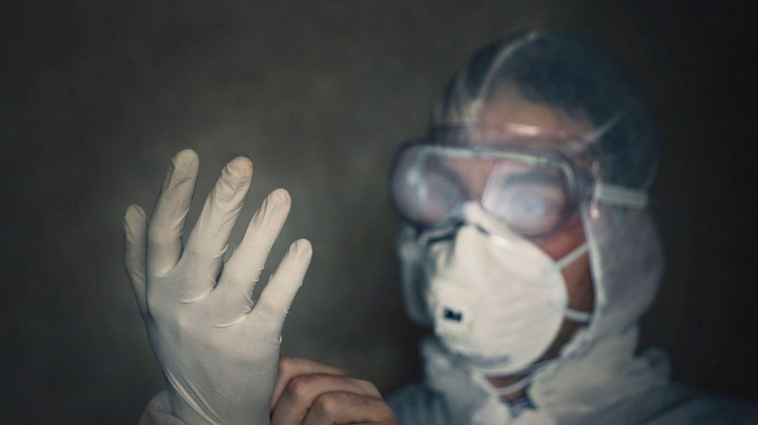Medic îmbrăcat în echipament de protecție anti-COVID, în întuneric.