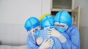 Medici îmbrăcați în combinezoane COVID, îmbrățișându-se.