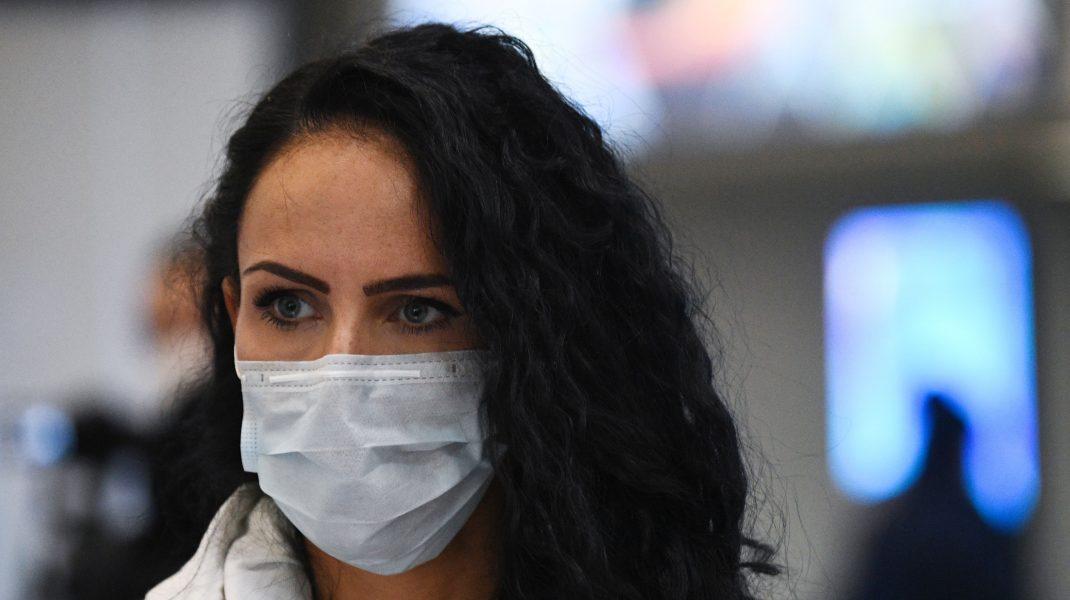 Femeie în aeroport care poartă o mască de protecție împotriva COVID-19.
