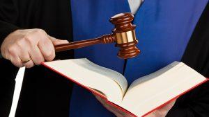 Judecător care ține în mână o carte și un ciocănel.
