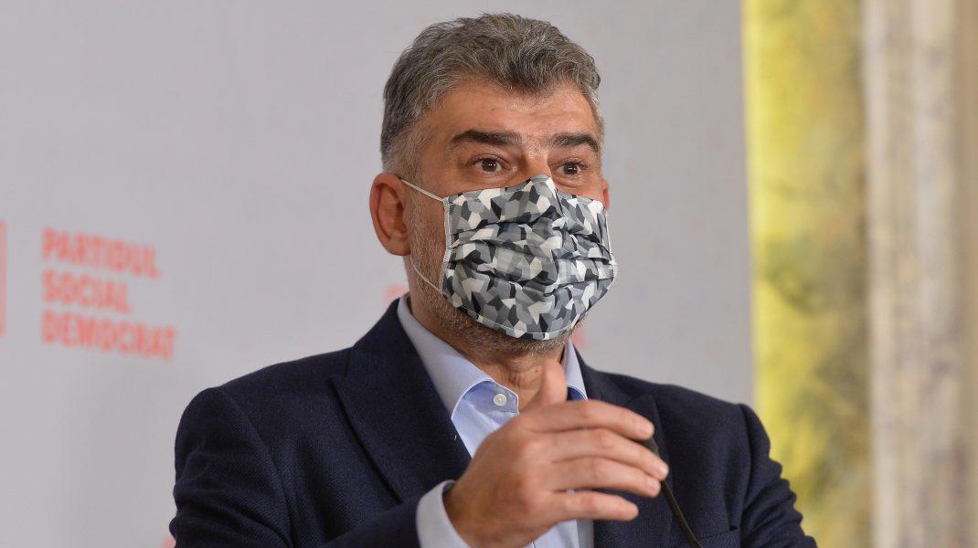 Marcel Ciolacu poartă mască de protecție în timp ce vorbește la microfon.