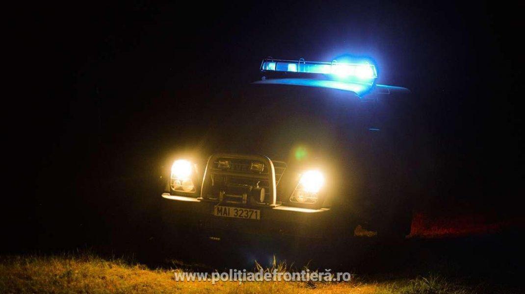 masina a politiei de frontiera, noaptea, cu farurile aprinse.
