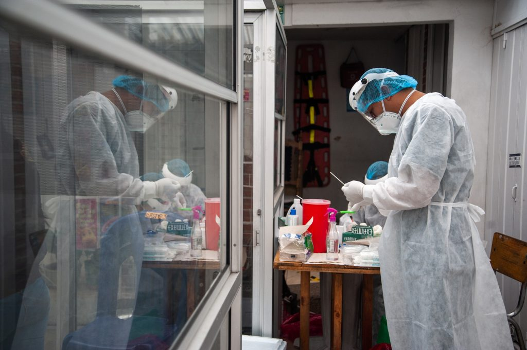 Medici îmbrăcați în echipament COVID care verifică teste de coronavirus.