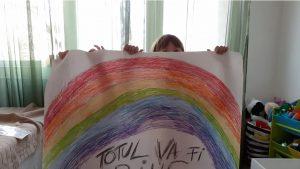Două fetițe arată un curcubeu pe care l-au colorat în timpul pandemiei