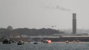 O rachetă de semnalizare este aprinsă în timp ce bărci de pescuit franceze protestează în fața portului Saint Helier, în largul insulei britanice Jersey.