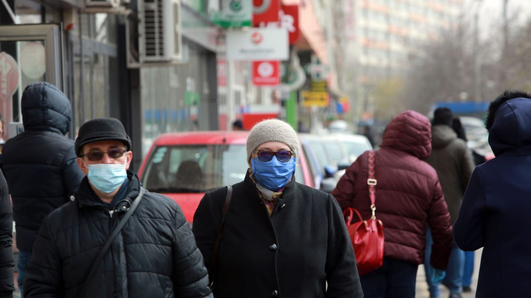Oameni bătrâni care se plimbă pe străzile din București și poartă mască de protecție.