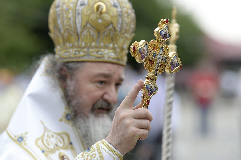 Preot care ține în mână o cruce.