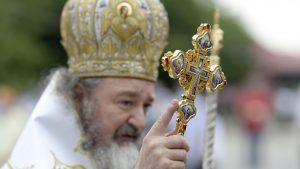 Preto care ține în mână o cruce.