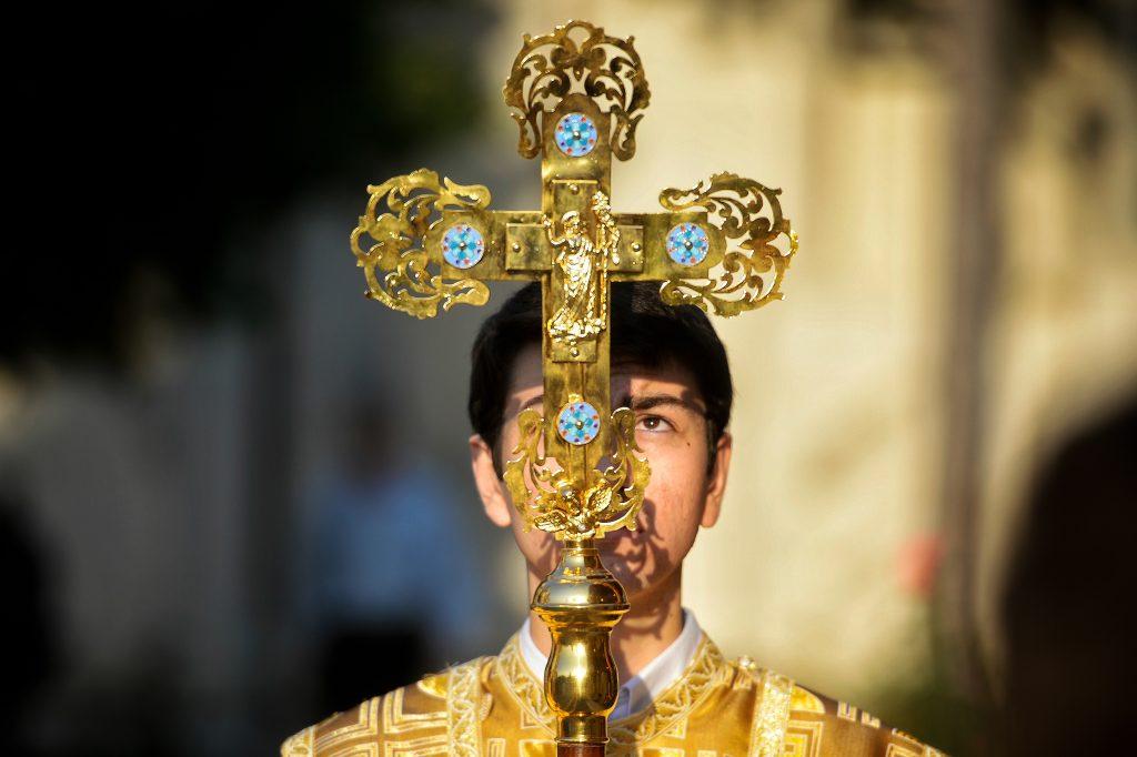 Pret care ține în mână Sfânta Cruce.