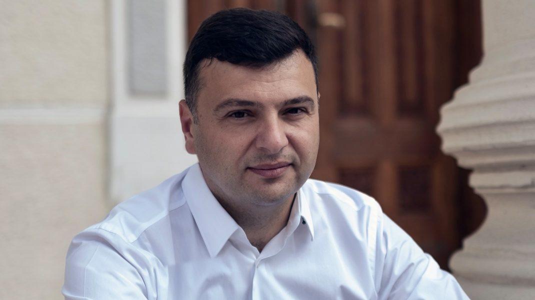 Sergiu Bîlcea, deputat PNL, pozând pe scările unei clădiri.