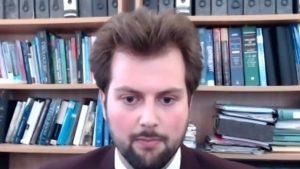 Ștefan Dascălu stă în fața unei biblioteci, la birou, într-un videocall.