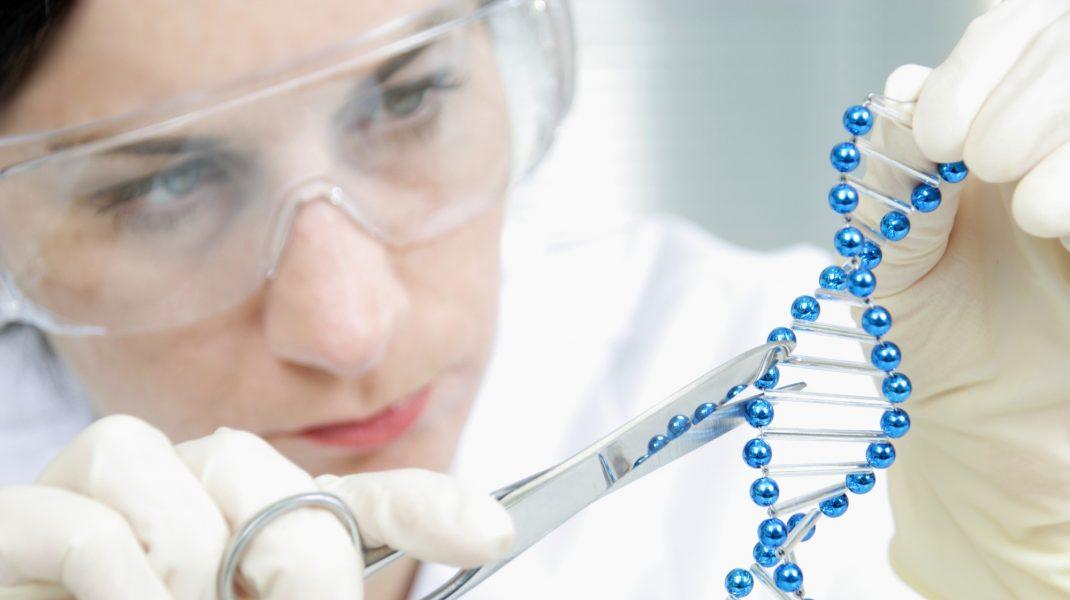 Femeie în laborator care lucrează cu un obiect care întruchipează ADN-ul.