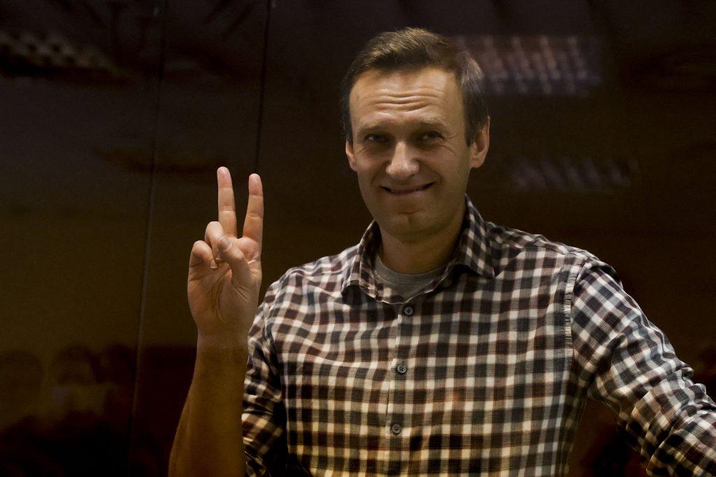 Alexey Navalnîi zâmbește și ridică două degete în semn de pace.