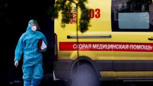 un angajat medical cu costum de protectie langa o ambulanta din rusia, moscova.