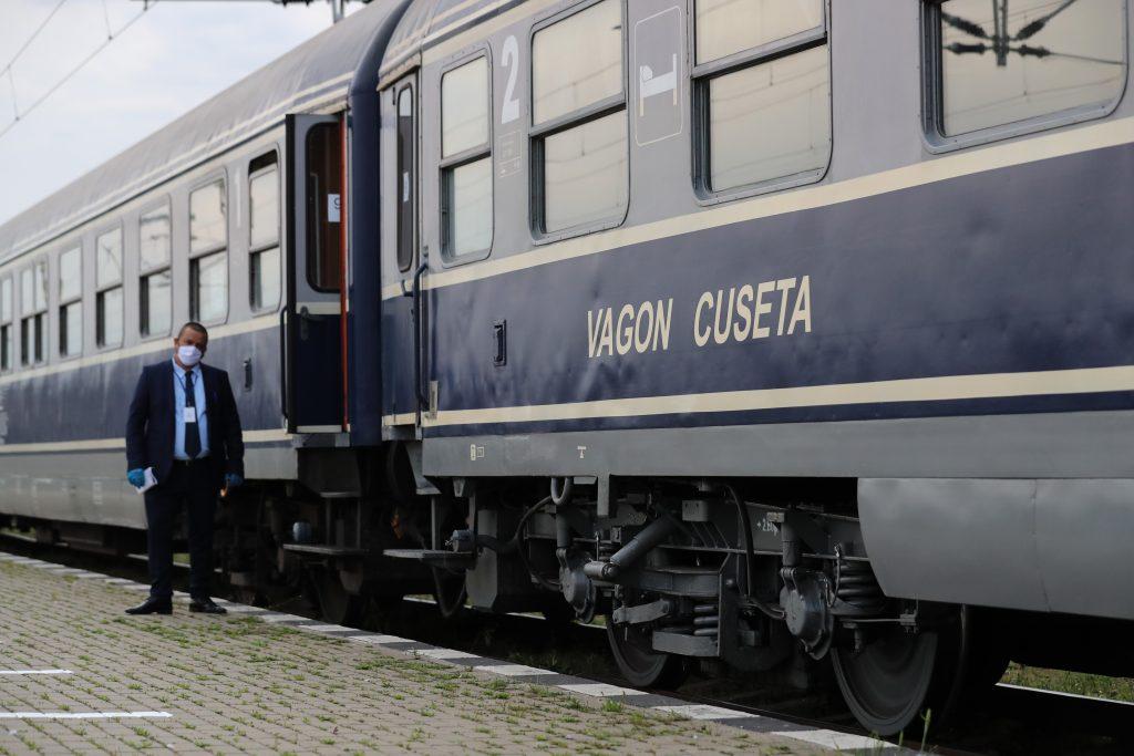 un controlor sta langa un tren de la cfr.