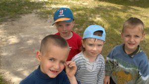 Copii orfani care se uită triști spre aparatul de fotografiat.