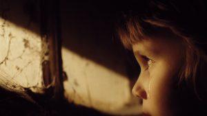 Copil care plânge într-o cameră întunecoasă.