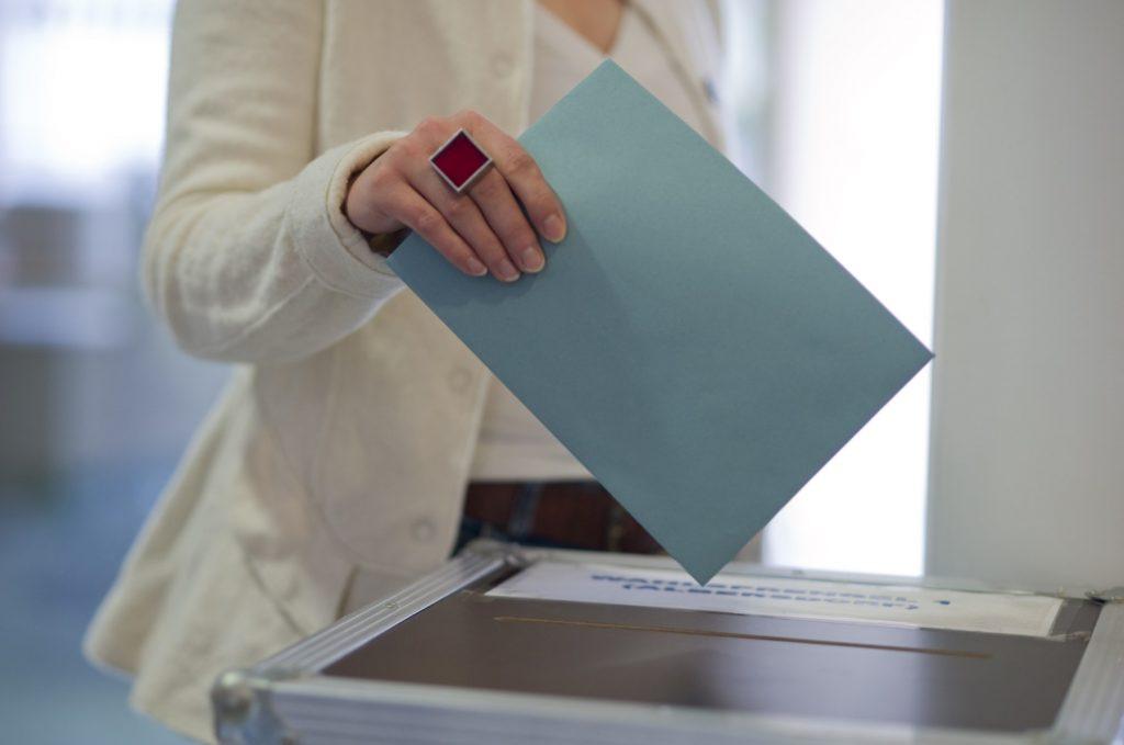 Femeie care depune un buletin de vot în urnă.