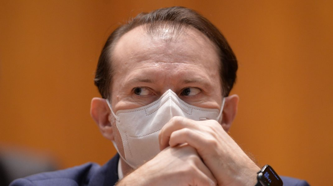 Florin Cîțu se uită pe sub sprâncene în timp ce își pune mâinile pe față.