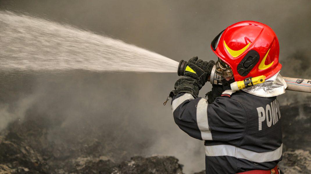 un pompier tine furtunul cu apa la un incendiu.
