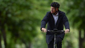 Klaus Iohannis merge pe bicicletă în parc.