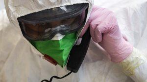 Medic în costum de protecție anti-COVID care vorbește la telefon printr-o mască.