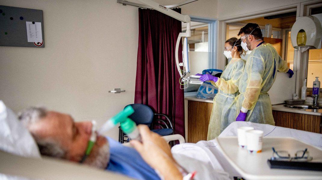 Pacient infectat cu COVID-19 într-un salon de spital, alături de doi doctori.